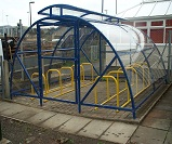 FS45 - Economy lockable closed compound cycle shelter for 20 bikes, with contrasting colour cycle racks and vented roof