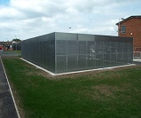 Installed Taurus High Security Compound Cycle shelter for 128 bikes at Winsford Academy, BREEAM 2008 specification, galvanised perforated steel sheet sidewalls, box profile galvanised steel roof sheeting
